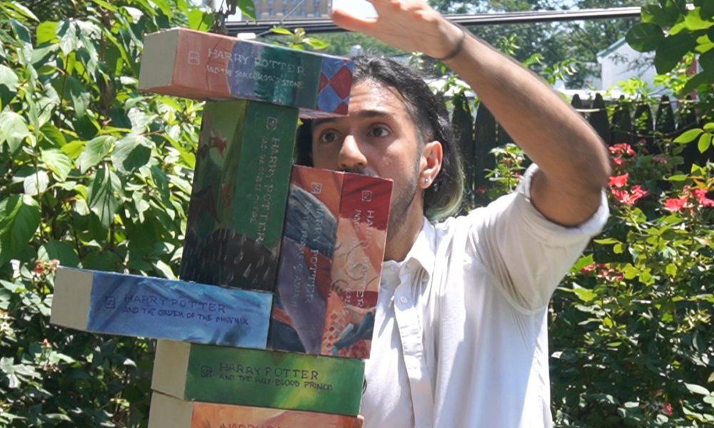 Joseph Ahmed balancing Harry Potter books