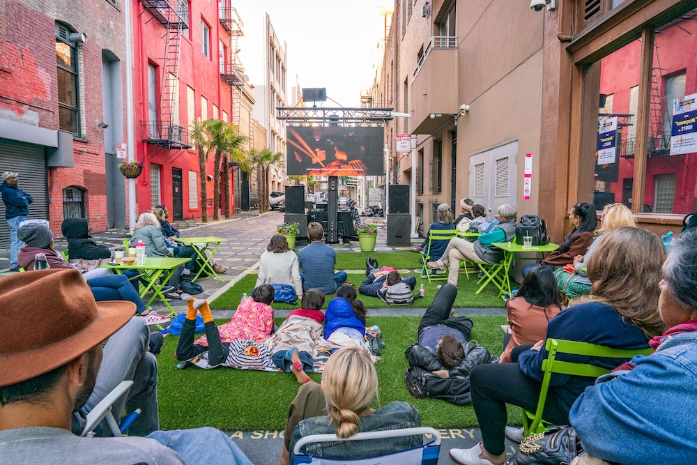 People sit and stand in an alley watching a film