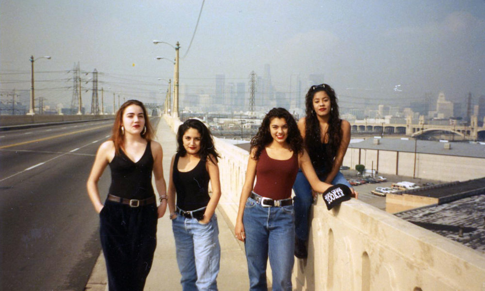 Four people face the camera with Los Angeles in the background