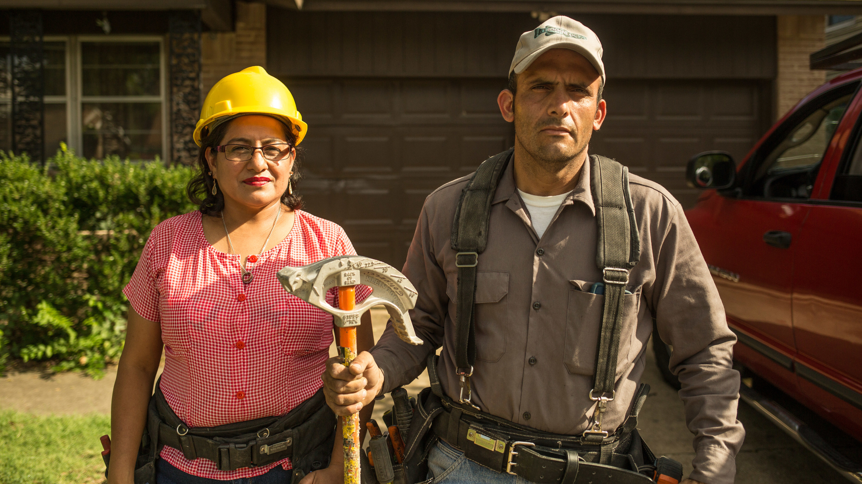 Person in hard hat next to person holding construction tool