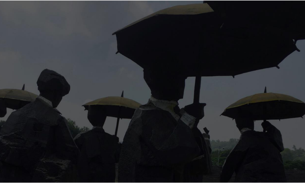 Dark silhouettes of people holding umbrellas