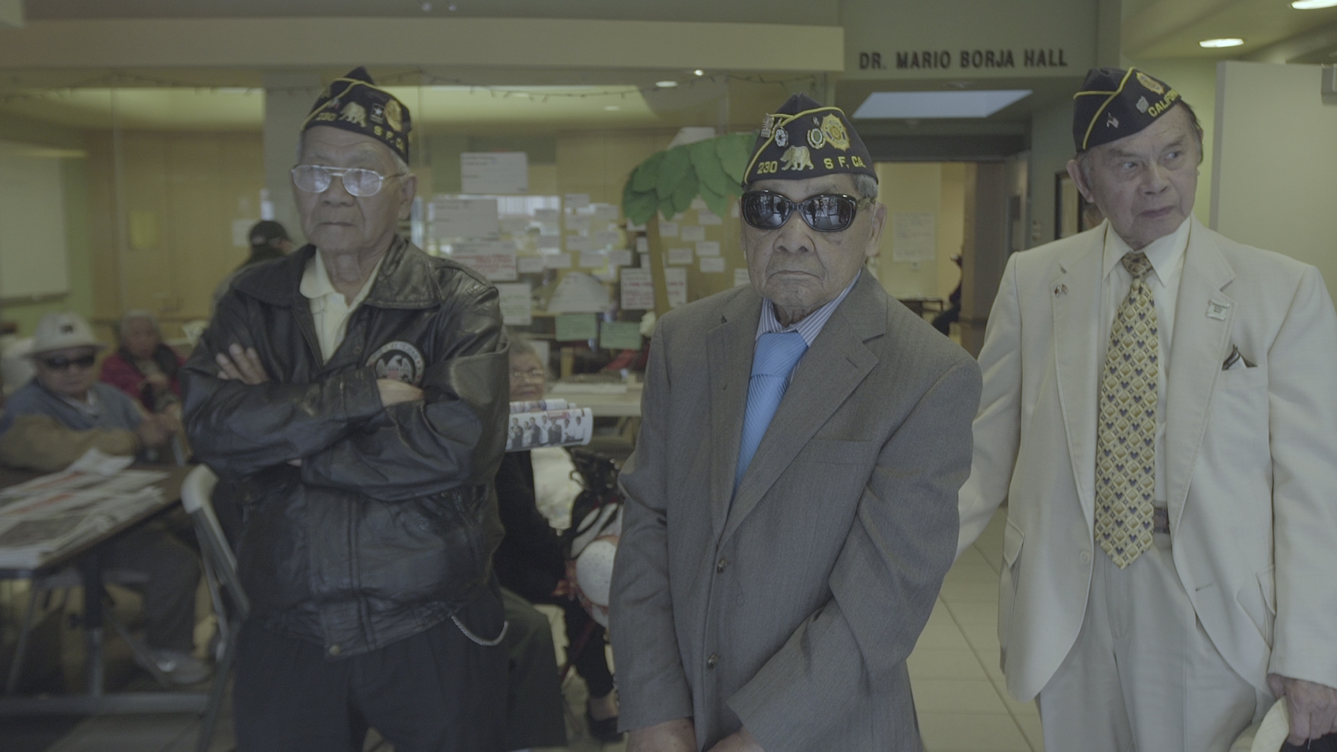 Three people stand wearing veteran hats