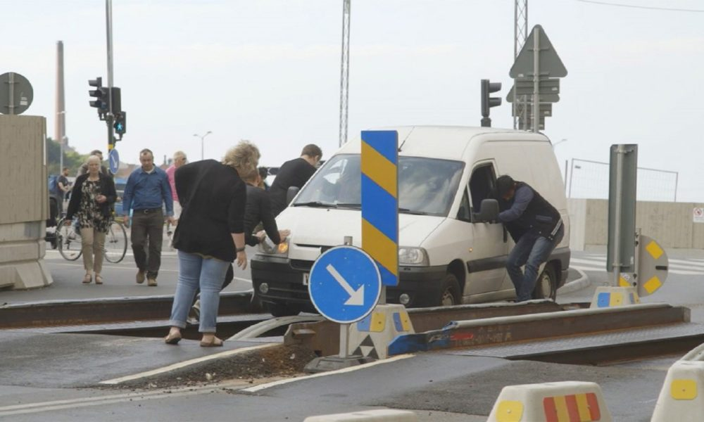 people surround a car passing through a roadway