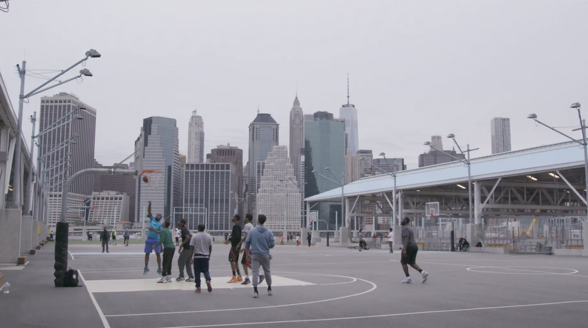 people play basketball with LA skyline in the background