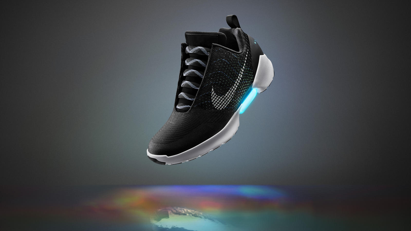 "Nike HyperAdapt 1.0 Manifests the Unimaginable ""Innovation at Nike is not about dreaming of tomorrow. It's about accelerating toward it,"" says Tinker Hatfield. ""We're able to anticipate the needs of athletes because we know them better than anybody. Sometimes, we deliver a reality before others have even begun to imagine it."" Welcome the Nike HyperAdapt 1.0, the first performance vehicle for Nike's latest platform breakthrough, adaptive lacing. The shoe translates deep research in digital, electrical and mechanical engineering into a product designed for movement. It challenges traditional understanding of fit, proposing an ultimate solution to individual idiosyncrasies in lacing and tension preference. Functional simplicity reduces a typical athlete concern, distraction. ""When you step in, your heel will hit a sensor and the system will automatically tighten,"" explains Tiffany Beers, Senior Innovator, NIKE, Inc., and the project's technical lead. ""Then there are two buttons on the side to tighten and loosen. You can adjust it until it's perfect."" For Hatfield, the innovation solves another enduring athlete-equipment quandary: the ability to make swift micro-adjustments. Undue pressure caused by tight tying and slippage resulting from loose laces are now relics of the past. Precise, consistent, personalized lockdown can now be manually adjusted on the fly. ""That's an important step, because feet undergo an incredible amount of stress during competition,"" he says. Beers began pondering the mechanics shortly after meeting Hatfield, who dreamed of making adaptive lacing a reality. He asked if she wanted to figure it out — not a replication of a preexisting idea but as ""the first baby step to get to a more sophisticated place."" The project caught the attention of a third collaborator, NIKE, Inc. President & CEO Mark Parker, who helped guide the design. The process saw Beers brainstorming with a group of engineers intent on testing her theories. They first came up with a snowboard boot featuring an external generator. While far from the ideal, it was the first of a series of strides toward Beers and Hatfield's original goal: to embed the technical components into such a small space that the design moves with the body and absorbs the same force the athlete is facing. Through 2013, Hatfield and Beers spearheaded a number of new systems, a pool of prototypes and several trials, arriving at an underfoot-lacing mechanism. In April 2015, Beers was tasked with making a self-lacing Nike Mag to celebrate the icon's true fictional release date of October 21. The final product quietly debuted Nike's new adaptive technology. Shortly after, the completion of the more technical, sport version they'd originally conceived, the Nike HyperAdapt 1.0, confirmed the strength of the apparatus. ""It's a platform,"" Beers says, ""something that helps envision a world in which product changes as the athlete changes."" The potential of adaptive lacing for the athlete is huge, Hatfield adds, as it would provide tailored-to-the-moment custom fit. ""It is amazing to consider a shoe that senses what the body needs in real-time. That eliminates a multitude of distractions, including mental attrition, and thus truly benefits performance."" He concludes, ""Wouldn't it be great if a shoe, in the future, could sense when you needed to have it tighter or looser? Could it take you even tighter than you'd normally go if it senses you really need extra snugness in a quick maneuver? That's where we're headed. In the future, product will come alive."" In short, the Nike HyperAdapt 1.0 is the first step into the future of adaptive performance. It's currently manual (i.e., athlete controlled) but it makes feasible the once-fantastic concept of an automated, nearly symbiotic relationship between the foot and shoe. The Nike HyperAdapt 1.0 will be available ONLY to members of Nike+ beginning Holiday 2016 in three colors. To become a Nike+ member and sign up for notifications about the Nike HyperAdapt 1.0, go to Nike.com."