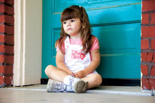 little girl sitting in front of blue door