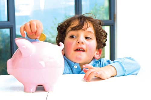 Little boy saving money in his piggy bank