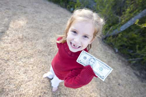 Girl holding money she got from the tooth fairy