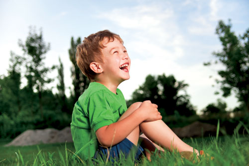 boy in green laughing outside
