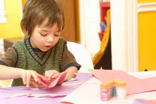 Preschool boy cutting with scissors
