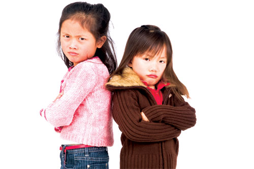 two young girls back to back arms folded fighting