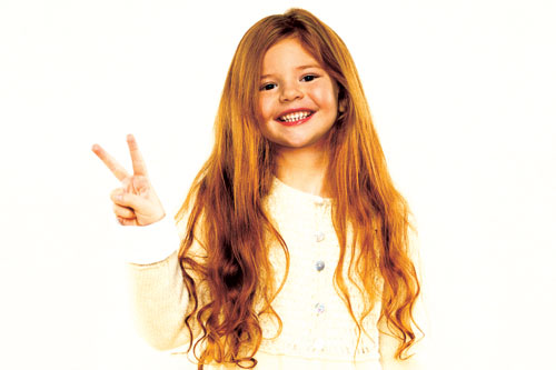 red-headed girl making peace sign and smiling with teeth