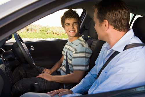 Teen boy driving with his dad