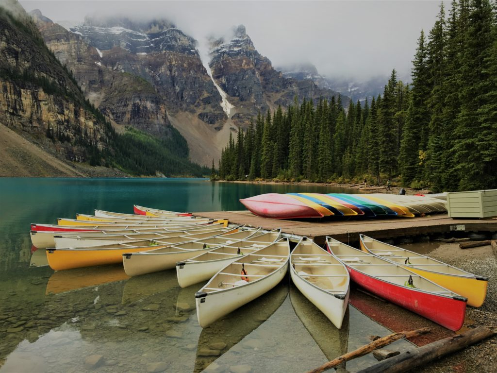 Canoes in the water and stacked on a pier, jutting out into a body of water surrounded by mountains.