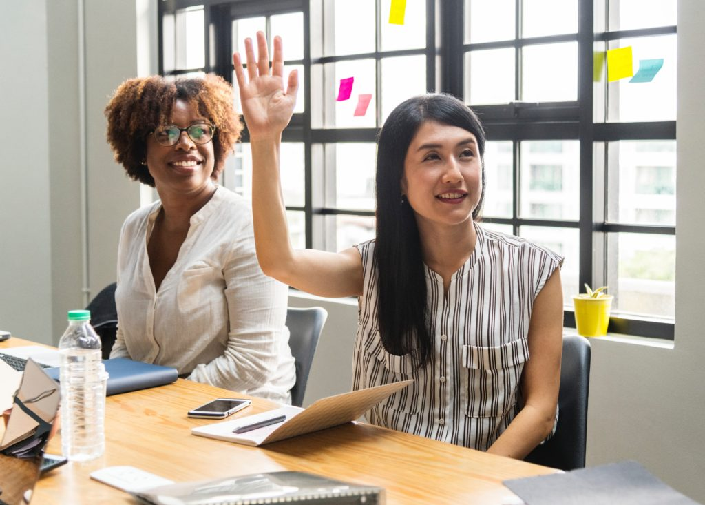 Two colleagues in a meeting space, one raising her hand for her turn to speak.