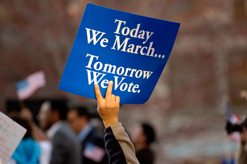 """A sign held aloft that reads """"Today We March... Tomorrow We Vote."""""""