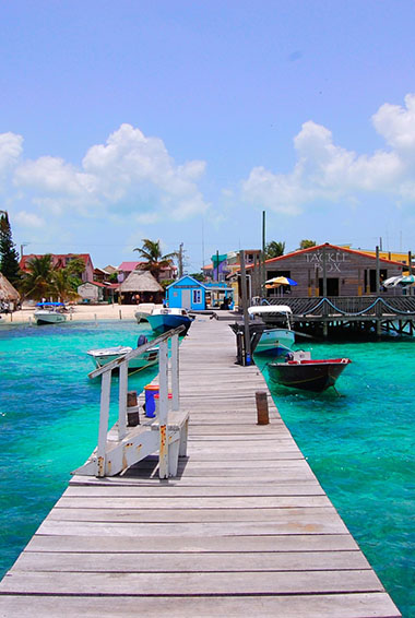 a dock in tropical blue waters looking inland toward a beach in Belize