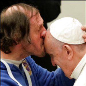 Pope tenderly kissed on forehead by man in front-row seat