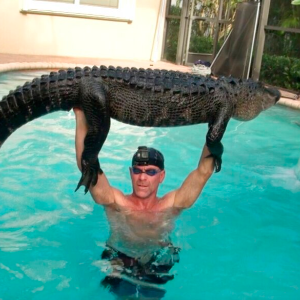 Trapper plays with 'gator until it tires, pulls it from pool