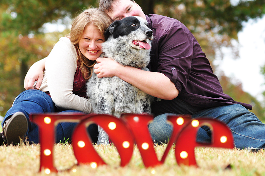 Couple hugging their dog