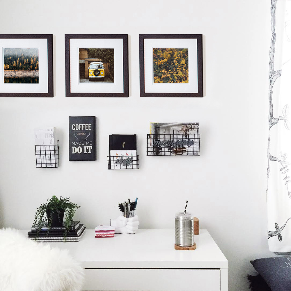 Framed prints over a desk