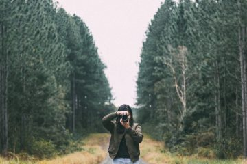 Female photographer stands in wooded path