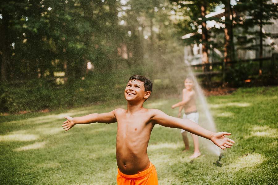 boy playing in sprinkler