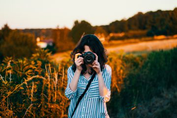 Young woman stands in field with a DSLR camera