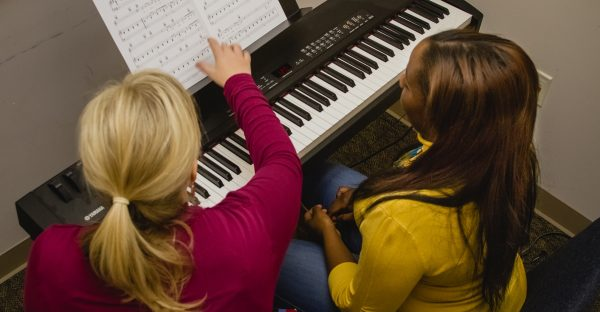 Student And Instructor At Piano In Music Class