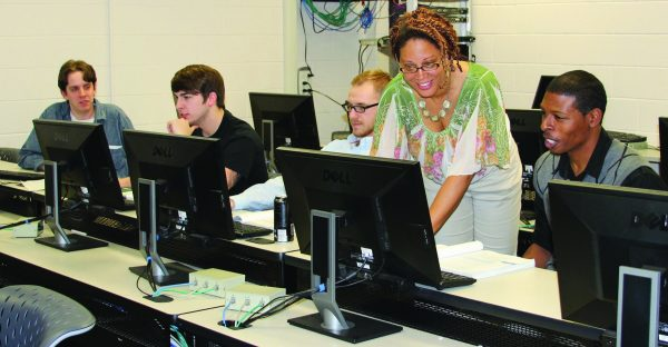 Instructor Assisting With Computer Assignment