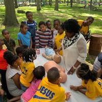 Dr. Grace teaching kids CPR.