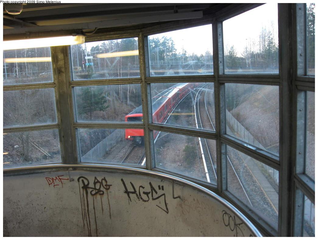 (221k, 1044x788)<br><b>Country:</b> Finland<br><b>City:</b> Helsinki<br><b>System:</b> Helsinki City Transport (HKL)<br><b>Line:</b> Helsinki Metro<br><b>Location:</b> Myllypuro (Kvarnbäcken) <br><b>Photo by:</b> Simo Melenius<br><b>Date:</b> 2/14/2007<br><b>Notes:</b> Surface station roofed by a steel frame. Stairs to platform level. Westbound train from Mellunmäki approaching the station.<br><b>Viewed (this week/total):</b> 2 / 503