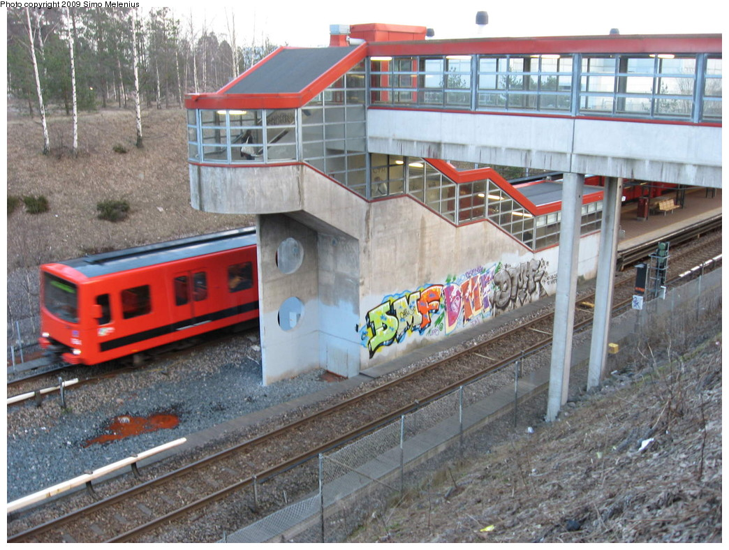 (268k, 1044x788)<br><b>Country:</b> Finland<br><b>City:</b> Helsinki<br><b>System:</b> Helsinki City Transport (HKL)<br><b>Line:</b> Helsinki Metro<br><b>Location:</b> Myllypuro (Kvarnbäcken) <br><b>Photo by:</b> Simo Melenius<br><b>Date:</b> 2/14/2007<br><b>Notes:</b> Surface station roofed by a steel frame. Pedestrian overpass connecting to the concrete staircase. Eastbound train to Mellunmäki pulling out from the station.<br><b>Viewed (this week/total):</b> 2 / 632