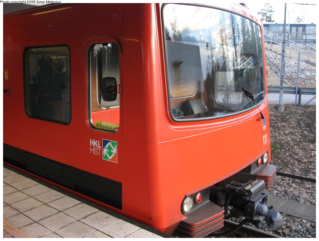 (234k, 1044x788)<br><b>Country:</b> Finland<br><b>City:</b> Helsinki<br><b>System:</b> Helsinki City Transport (HKL)<br><b>Line:</b> Helsinki Metro<br><b>Location:</b> Kontula (Gårdsbacka) <br><b>Photo by:</b> Simo Melenius<br><b>Date:</b> 2/14/2007<br><b>Notes:</b> Surface station partially under street bridges and a shopping centre, partially covered by concrete and steel roofs. The tail-end of a Mellunmäki train standing on the eastbound platform. The single two-car unit can be driven from both ends. All services are provided by 2-3 coupled units, giving the length of 4-6 cars.<br><b>Viewed (this week/total):</b> 1 / 572