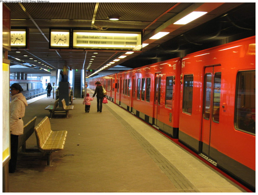 (236k, 1044x788)<br><b>Country:</b> Finland<br><b>City:</b> Helsinki<br><b>System:</b> Helsinki City Transport (HKL)<br><b>Line:</b> Helsinki Metro<br><b>Location:</b> Kontula (Gårdsbacka) <br><b>Photo by:</b> Simo Melenius<br><b>Date:</b> 2/14/2007<br><b>Notes:</b> Surface station partially under street bridges and a shopping centre, partially covered by concrete and steel roofs. Train standing on the westbound platform to Ruoholahti. Kontula has an island platform like most other stations in Helsinki Metro.<br><b>Viewed (this week/total):</b> 3 / 602