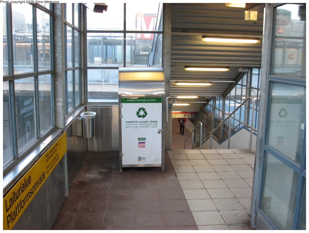 (226k, 1044x788)<br><b>Country:</b> Finland<br><b>City:</b> Helsinki<br><b>System:</b> Helsinki City Transport (HKL)<br><b>Line:</b> Helsinki Metro<br><b>Location:</b> Kontula (Gårdsbacka) <br><b>Photo by:</b> Simo Melenius<br><b>Date:</b> 2/14/2007<br><b>Notes:</b> Surface station partially under street bridges and a shopping centre, partially covered by concrete and steel roofs. Western entrance to the platforms. Dating back to the time when the whole Mellunmäki branch was built, it is a bit tight in space and lacks the large, airy design that is present in the more modern construction.<br><b>Viewed (this week/total):</b> 1 / 491