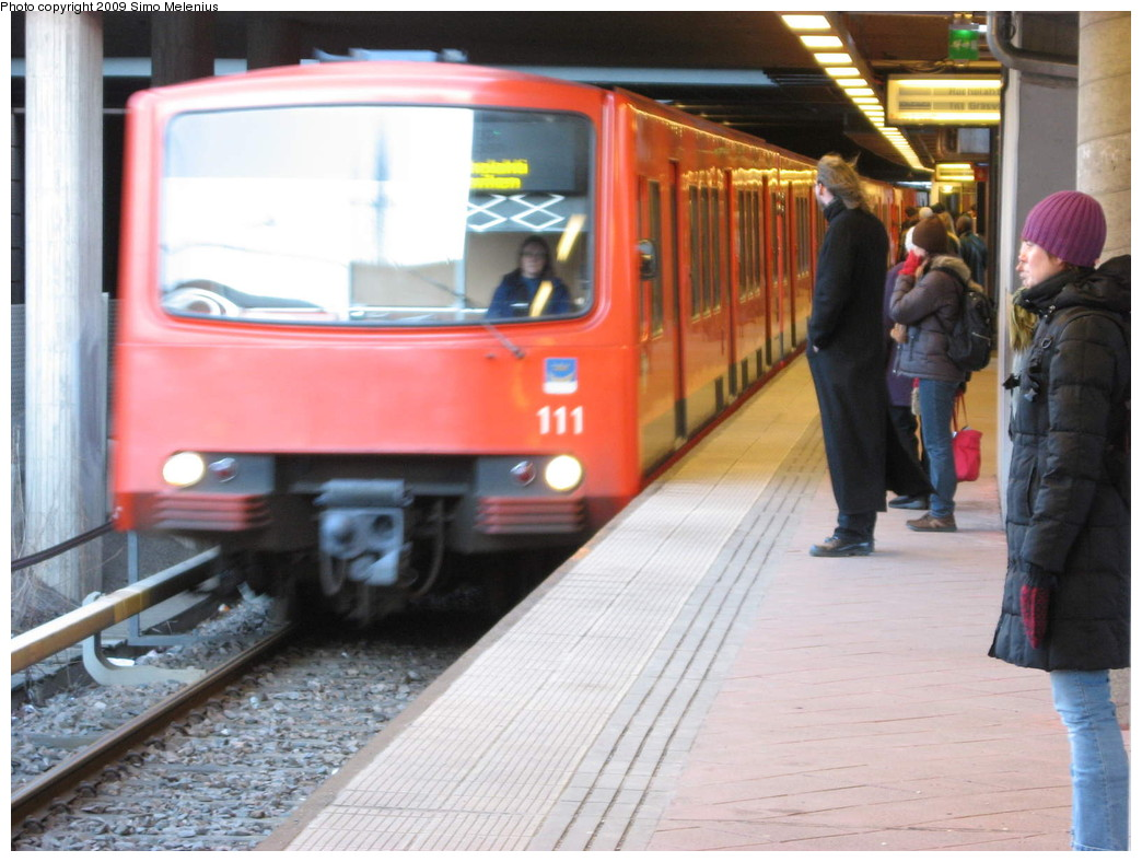 (206k, 1044x788)<br><b>Country:</b> Finland<br><b>City:</b> Helsinki<br><b>System:</b> Helsinki City Transport (HKL)<br><b>Line:</b> Helsinki Metro<br><b>Location:</b> Kontula (Gårdsbacka) <br><b>Photo by:</b> Simo Melenius<br><b>Date:</b> 2/14/2007<br><b>Notes:</b> Surface station partially under street bridges and a shopping centre, partially covered by concrete and steel roofs. Train from Mellunmäki pulling in to the westbound platform, entering to the open-air section of the station.<br><b>Viewed (this week/total):</b> 1 / 503