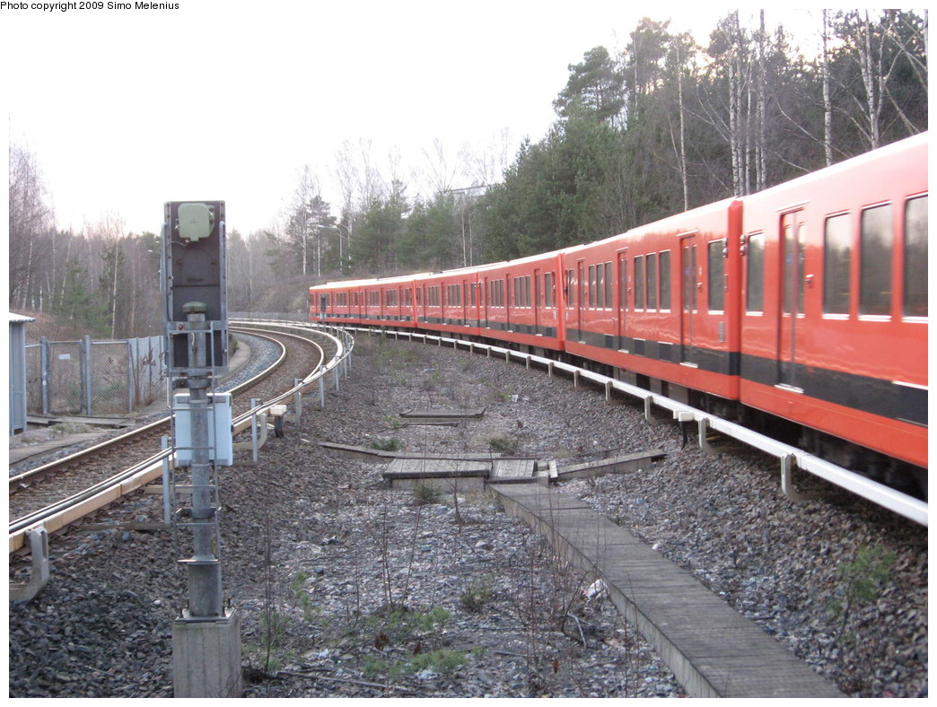 (268k, 1044x788)<br><b>Country:</b> Finland<br><b>City:</b> Helsinki<br><b>System:</b> Helsinki City Transport (HKL)<br><b>Line:</b> Helsinki Metro<br><b>Location:</b> Kontula (Gårdsbacka) <br><b>Photo by:</b> Simo Melenius<br><b>Date:</b> 2/14/2007<br><b>Notes:</b> Surface station partially under street bridges and a shopping centre, partially covered by concrete and steel roofs. View to west from Kontula station. A westbound train to Ruoholahti has just left the station and is speeding towards Myllypuro.<br><b>Viewed (this week/total):</b> 0 / 680