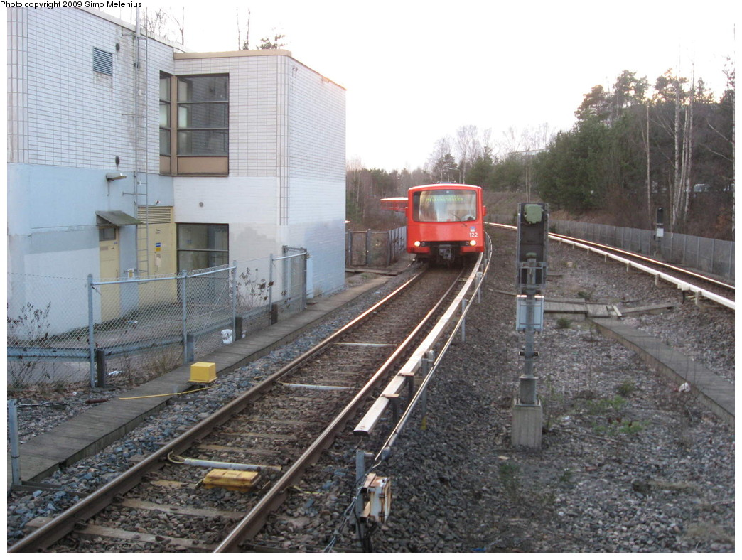 (246k, 1044x788)<br><b>Country:</b> Finland<br><b>City:</b> Helsinki<br><b>System:</b> Helsinki City Transport (HKL)<br><b>Line:</b> Helsinki Metro<br><b>Location:</b> Kontula (Gårdsbacka) <br><b>Photo by:</b> Simo Melenius<br><b>Date:</b> 2/14/2007<br><b>Notes:</b> Surface station partially under street bridges and a shopping centre, partially covered by concrete and steel roofs. An eastbound train to Mellunmäki on the approach to Kontula station.<br><b>Viewed (this week/total):</b> 1 / 582