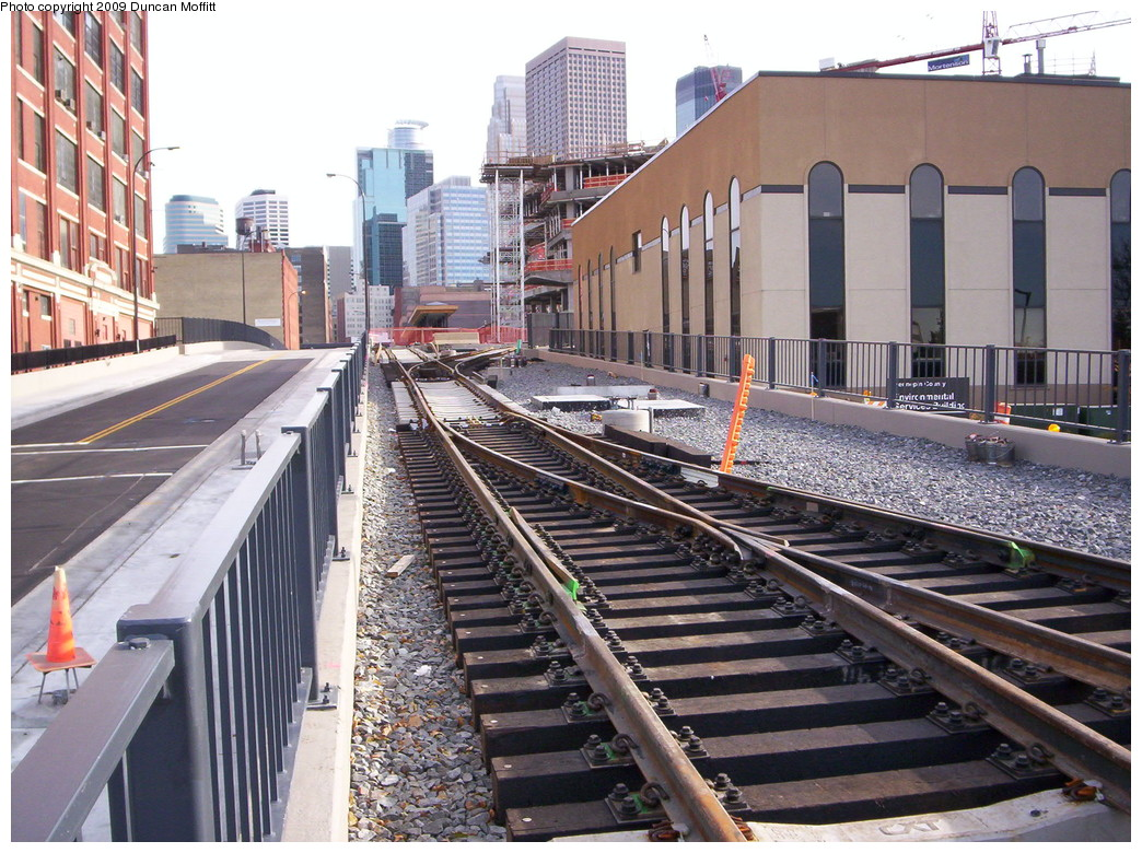 (285k, 1044x780)<br><b>Country:</b> United States<br><b>City:</b> Minneapolis, MN<br><b>System:</b> MNDOT Light Rail Transit<br><b>Line:</b> Hiawatha Line<br><b>Location:</b> <b>Downtown Minneapolis Ballpark</b> <br><b>Photo by:</b> Duncan Moffitt<br><b>Date:</b> 11/1/2008<br><b>Notes:</b> Looking southeastward on N. 5th St, toward DT Mpls/Ballpark station, which is just beyond the orange webbing stretched across the tracks.  Trackage in the foreground is nonrevenue, to be used for layovers. Note the unusual bottleneck switching arrangement.<br><b>Viewed (this week/total):</b> 0 / 749
