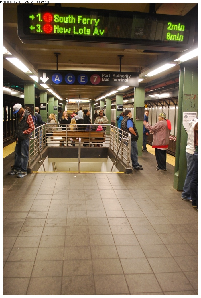 (280k, 705x1044)<br><b>Country:</b> United States<br><b>City:</b> New York<br><b>System:</b> New York City Transit<br><b>Line:</b> IRT West Side Line<br><b>Location:</b> Times Square/42nd Street <br><b>Photo by:</b> Lee Winson<br><b>Date:</b> 3/18/2012<br><b>Notes:</b> IRT Seventh Ave, 42nd-Times Square, platform and waiting time sign.  Arrows point to appropriate track for train.<br><b>Viewed (this week/total):</b> 0 / 1142