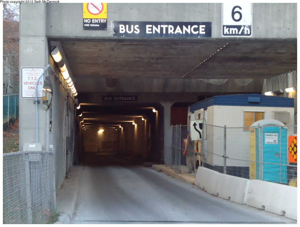 (278k, 1044x788)<br><b>Country:</b> Canada<br><b>City:</b> Toronto<br><b>System:</b> TTC<br><b>Line:</b> TTC Yonge-University-Spadina Subway<br><b>Location:</b> Lawrence <br><b>Photo by:</b> Seth McDermott<br><b>Date:</b> 12/6/2012<br><b>Notes:</b> Bus terminal entrance on the north side of Lawrence Avenue ... view down the tunnel Buses drive on the left through the station so that a single center island platform can serve for both directions. Here the construction hut is blocking one lane; the sign behind it reads BUS EXIT. Note the keep left graphic sign on the median.<br><b>Viewed (this week/total):</b> 1 / 423