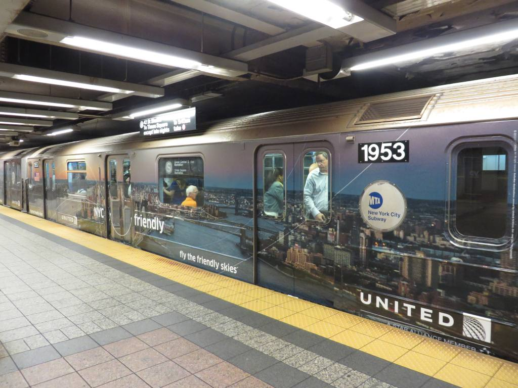 (132k, 1024x768)<br><b>Country:</b> United States<br><b>City:</b> New York<br><b>System:</b> New York City Transit<br><b>Line:</b> IRT Times Square-Grand Central Shuttle<br><b>Location:</b> Grand Central <br><b>Route:</b> S<br><b>Car:</b> R-62A (Bombardier, 1984-1987)  1953 <br><b>Photo by:</b> Robbie Rosenfeld<br><b>Date:</b> 10/3/2013<br><b>Notes:</b> United ad wrap<br><b>Viewed (this week/total):</b> 0 / 704
