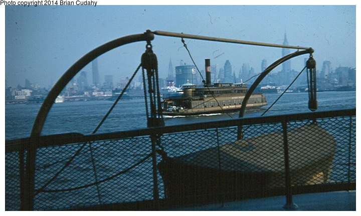 (138k, 720x431)<br><b>Country:</b> United States<br><b>System:</b> New York Central <br><b>Photo by:</b> Brian J. Cudahy<br><b>Notes:</b> Seen from the upper deck of a NYC ferryboat, another boat makes its way across the Hudson to Weehawken. Ocean liner in the background is the SS United States. 1959.<br><b>Viewed (this week/total):</b> 2 / 1564