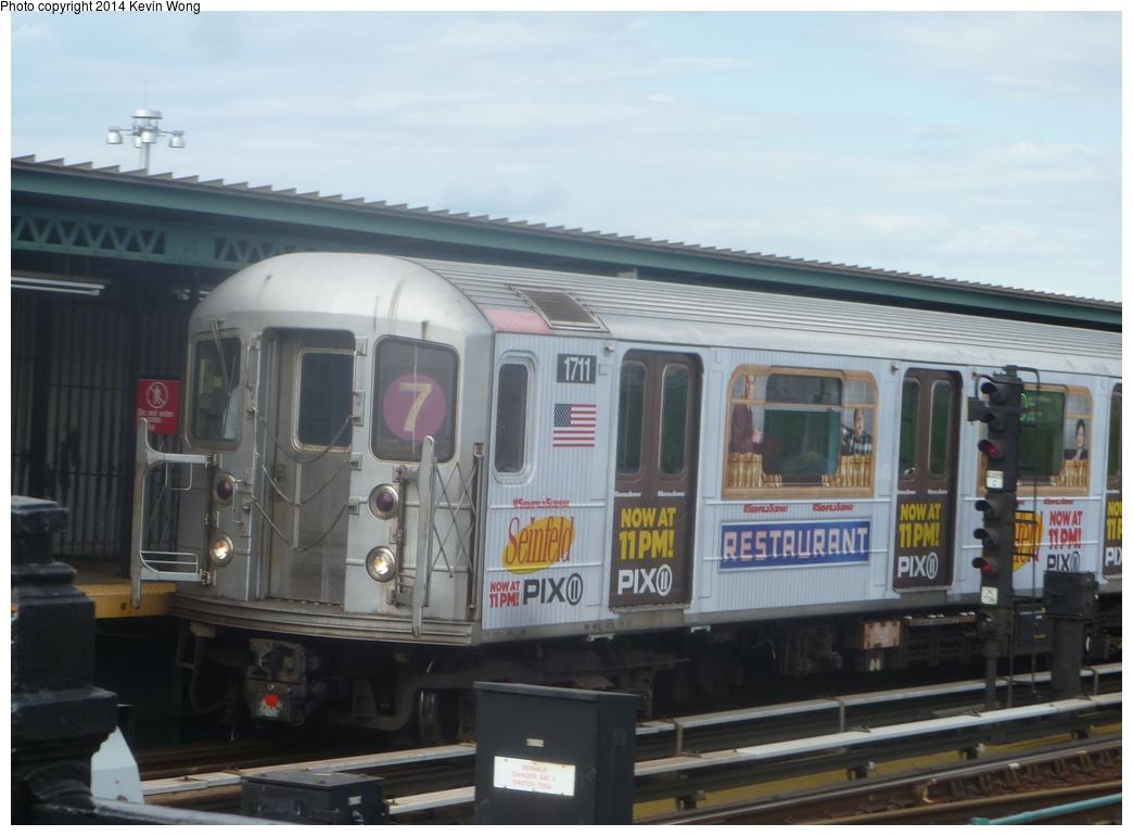 (238k, 1044x770)<br><b>Country:</b> United States<br><b>City:</b> New York<br><b>System:</b> New York City Transit<br><b>Line:</b> IRT Flushing Line<br><b>Location:</b> Willets Point/Mets (fmr. Shea Stadium) <br><b>Route:</b> 7<br><b>Car:</b> R-62A (Bombardier, 1984-1987)  1711 <br><b>Photo by:</b> Kevin Wong<br><b>Date:</b> 5/18/2014<br><b>Notes:</b> Seinfeld ad wrap<br><b>Viewed (this week/total):</b> 1 / 908