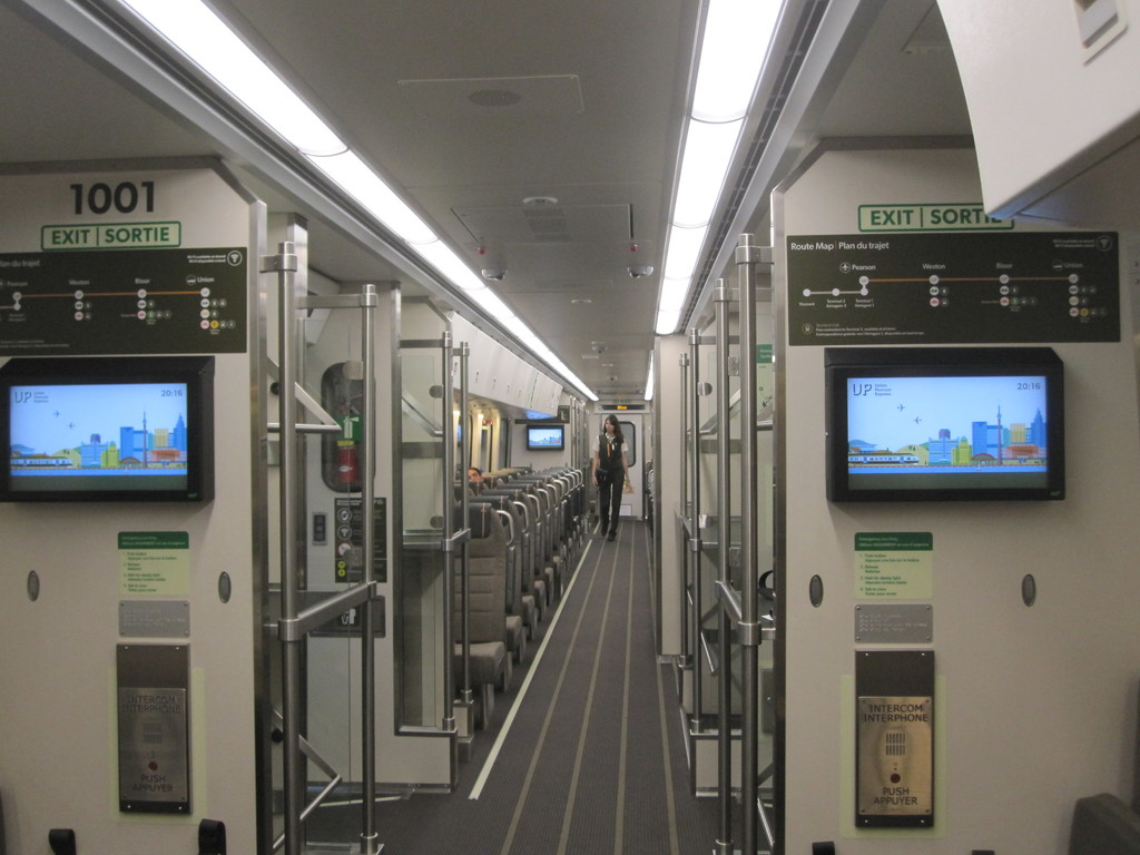 (164k, 1024x768)<br><b>Country:</b> Canada<br><b>City:</b> Toronto<br><b>System:</b> Union-Pearson Express<br><b>Photo by:</b> Collection of nycsubway.org<br><b>Date:</b> 6/8/2015<br><b>Notes:</b> Train interior, with crew member; luggage area and video screens in foreground.<br><b>Viewed (this week/total):</b> 1 / 1367