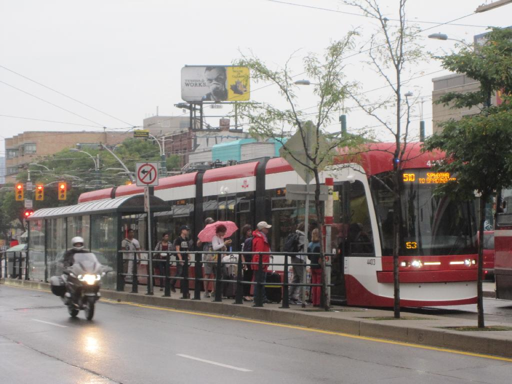 (112k, 1024x768)<br><b>Country:</b> Canada<br><b>City:</b> Toronto<br><b>System:</b> TTC<br><b>Line:</b> TTC 510-Spadina<br><b>Location:</b> Spadina/College <br><b>Car:</b> TTC Flexity Outlook (Bombardier, 2009-)  4403 <br><b>Photo by:</b> Collection of nycsubway.org <br><b>Date:</b> 9/10/2014<br><b>Notes:</b> Flexity car 4403 makes a northbound stop on a wet day. The first of these cars entered service 11 days before.<br><b>Viewed (this week/total):</b> 2 / 601
