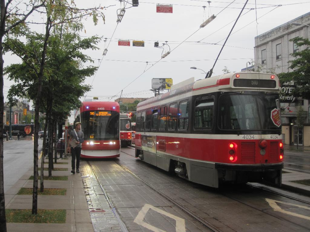 (133k, 1024x768)<br><b>Country:</b> Canada<br><b>City:</b> Toronto<br><b>System:</b> TTC<br><b>Line:</b> TTC 510-Spadina<br><b>Location:</b> Spadina/College <br><b>Car:</b> TTC Flexity Outlook (Bombardier, 2009-)  4403,4184,4034 <br><b>Photo by:</b> Collection of nycsubway.org <br><b>Date:</b> 9/10/2014<br><b>Notes:</b> Flexity car 4403 makes a northbound stop as two CLRVs pass by southbound and a third one is just visible on College St.  The red overhead signs read CAUTION - GROUND STRAP MAY BE INSTALLED - TEST BEFORE INSTALLING JUMPER and the other one is CAUTION - SECTION INSULATOR - Pass under with POWER OFF.<br><b>Viewed (this week/total):</b> 1 / 464