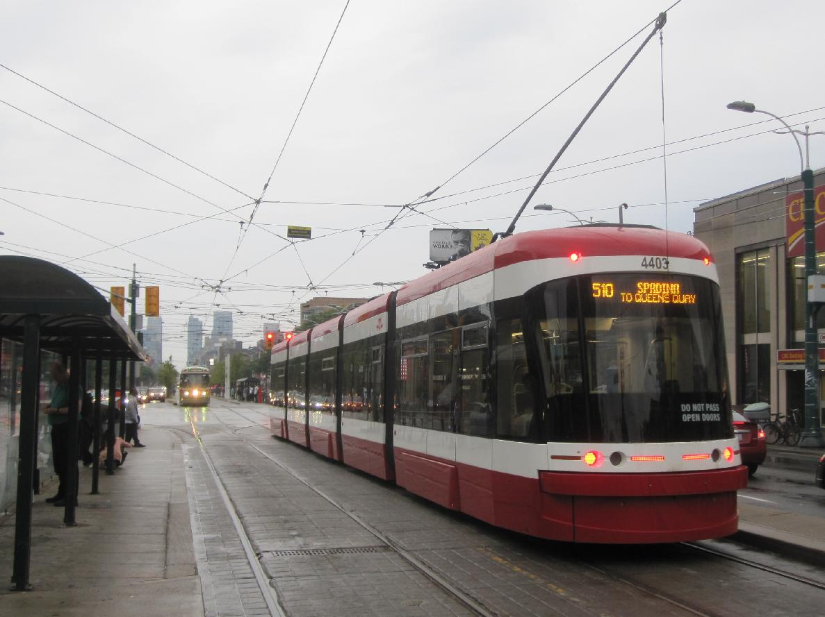 (117k, 1187x889)<br><b>Country:</b> Canada<br><b>City:</b> Toronto<br><b>System:</b> TTC<br><b>Line:</b> TTC 510-Spadina<br><b>Location:</b> Spadina/College <br><b>Car:</b> TTC CLRV 4022,4403 <br><b>Photo by:</b> Collection of nycsubway.org <br><b>Date:</b> 9/10/2014<br><b>Notes:</b> Northbound CLRV 4022 and southbound Flexity car 4403 each wait for the traffic light before crossing the intersection to reach their respective stops.<br><b>Viewed (this week/total):</b> 2 / 544