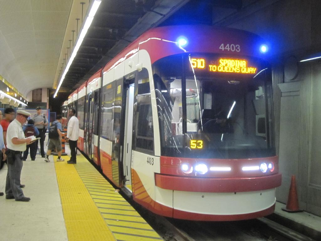 (103k, 1024x768)<br><b>Country:</b> Canada<br><b>City:</b> Toronto<br><b>System:</b> TTC<br><b>Line:</b> TTC 510-Spadina<br><b>Location:</b> Spadina Station <br><b>Car:</b> TTC Flexity Outlook (Bombardier, 2009-)  4403 <br><b>Photo by:</b> Collection of nycsubway.org <br><b>Date:</b> 9/10/2014<br><b>Notes:</b> Flexity car 4403 at the platform with a CLRV behind. The car is running only as far as Queens Quay because of a major project to rebuild Queens Quay and its tracks.<br><b>Viewed (this week/total):</b> 1 / 602